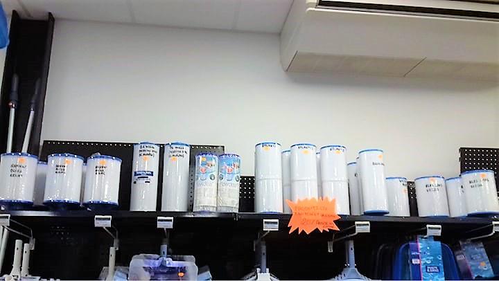 Etagère dans magasin présentant différents filtres pour spas