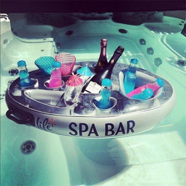Bar gonflable flottant dans un spa, rempli de bouteilles
